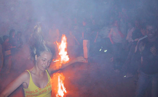 Pretty young girl jumping the fires of Saint John in Ikaria