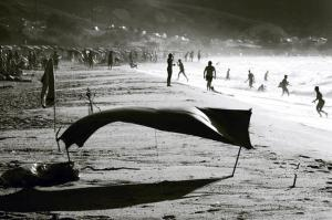 the crowded beach, the tent and the waves